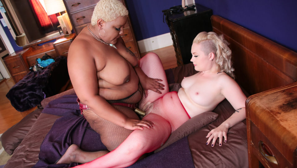Marshmallow girls volume 04 scene 02. Denali Winter and Cinnamon Maxxine are playful, fleshy girls with tattoos, piercings, large natural titties and lascivious net stockings. Maxxine is a mocha-black BBW with a short blonde Afro; creamy-white Denali has a china doll face and a shaved-side hairdo. They caress and kiss on the bed, heating up as they finger each other's shaved pussy. Denali sits on Cinnamon's face for cunnilingus, and Cinnamon's lipstick makes Denali's labia red! Denali rides Cinnamon's strap-on, cheeks jiggling, and Cinnamon gets on top for an intimate, face-to-face fuck. She sits, enveloping Denali's face in elegant ass, and Denali sees how long she can hold her breath in there. This is relaxed, ultra-real sapphic BBW action.